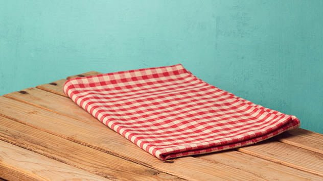 Empty wooden corner table with red checked tablecloth